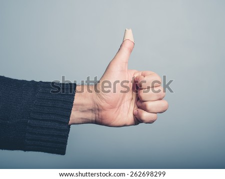 The hand of a young man is gesturing thumbs up with a plaster covering a wound on his thumb - stock photo