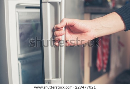 The hand of a young man is opening a freezer door - stock photo