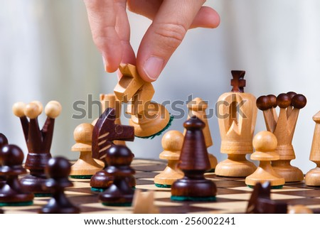 the hand of chess player with knight - stock photo
