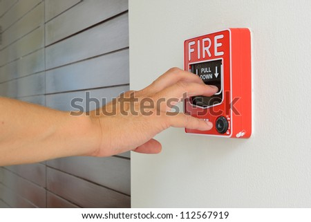 The hand of man is pulling fire alarm on the wall next to the door - stock photo