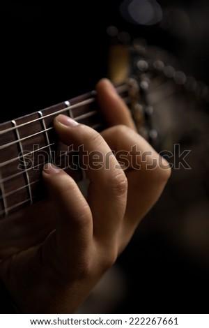 The hand of man playing guitar closeup - stock photo