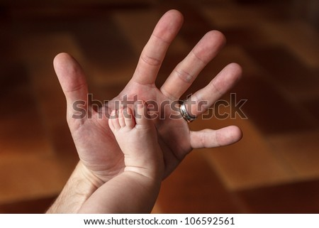 the hand of the father and the son's foot - stock photo