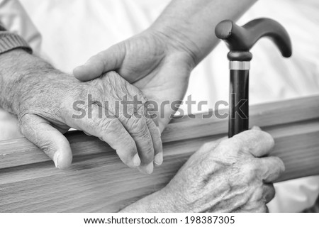 The hand of the old man and his daughter in the fifties, next to the hospital bed. Blur the edges. Focus on an old hand. Black and White. Small depth of field.  - stock photo