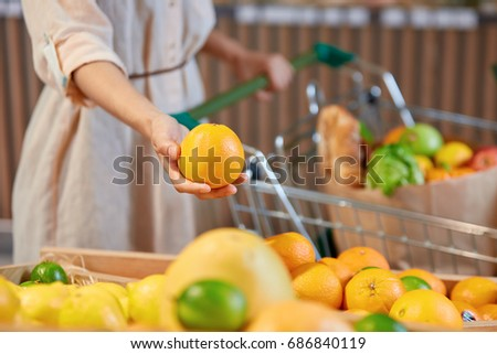 The hand of unidentified woman holding orange standing next to  vegetable stand and with cart full of useful organic super food