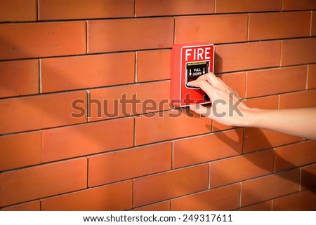 The hand of woman is pulling fire alarm on the brick wall - stock photo