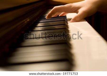 The hand on piano keyboard - stock photo