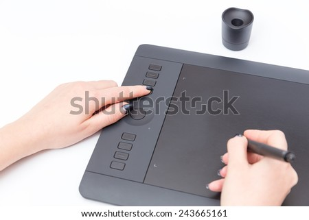 The hand presses the button on the tablet and draw on it a special pen