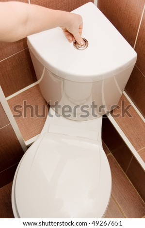 The hand presses the toilet bowl button - stock photo