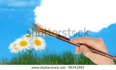 The hand with a brush draws a landscape.The blue sky and camomiles in the field - stock photo
