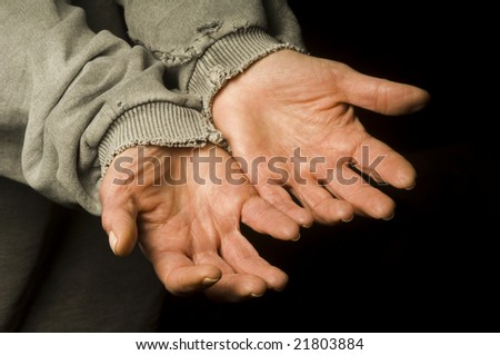 the hands of a beggar in an old shirt
