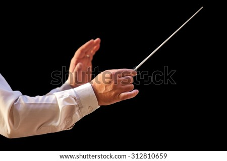 The hands of a conductor on a black background - stock photo