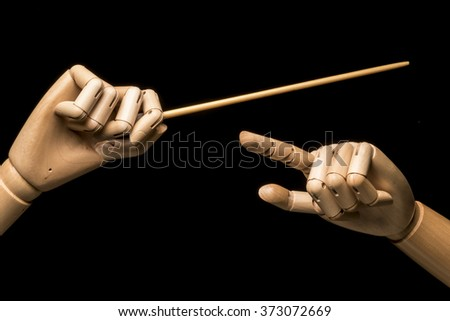 The hands of a conductor. One hand holds the baton, the other hand indicates the nuances. On black background.
