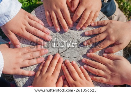 The hands of a few children over an old trunk with the word Love in the center of them - stock photo