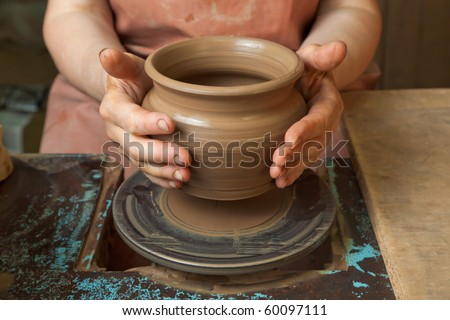 The hands of a potter, creating an earthen jar on the circle, close-ups - stock photo