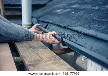 The hands of a worker fixing a drain from a scaffold - stock photo