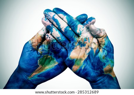 the hands of a young man put together patterned with a world map (furnished by NASA), slight vignette added - stock photo