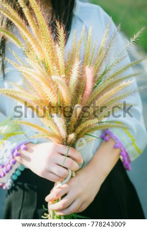 The hands of a young woman are holding a light brown bouquet of tender and tender flowers.