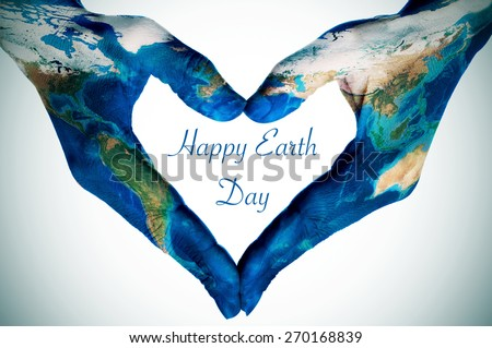 the hands of a young woman forming a heart patterned with a world map (furnished by NASA) and the text happy earth day - stock photo