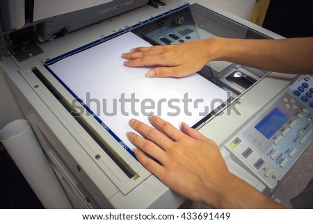 The hands of a young woman is placing a piece of paper on a flatbed scanner in preparation for copying it