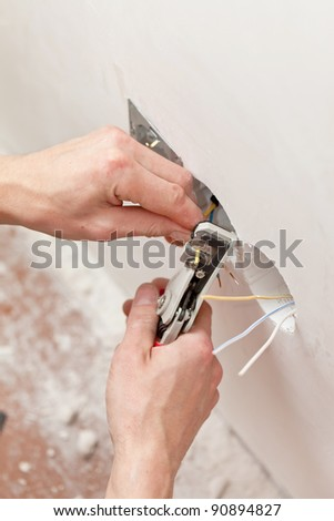 The hands of an electrician - stock photo