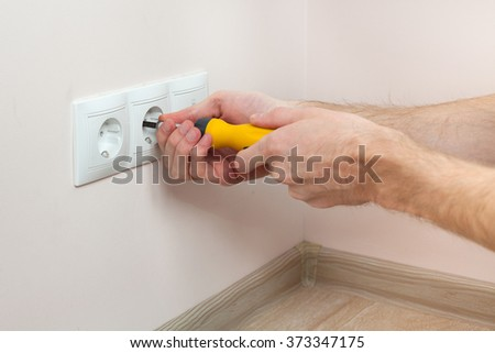 The hands of an electrician installing a wall power socket - stock photo