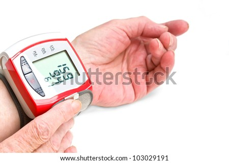 The hands of an old woman measuring blood pressure with a wrist meter. - stock photo