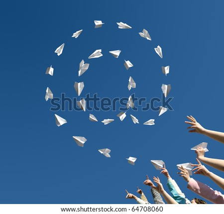 The Hands of children throw upwards little paper airplanes which are formed in the manner of symbol of e-mail.