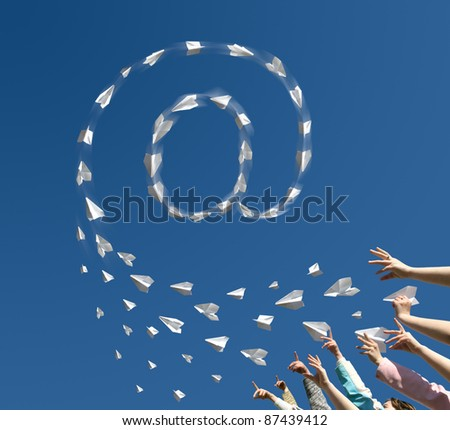 The Hands of children throw upwards little paper airplanes which are formed in the manner of symbol of e-mail. - stock photo