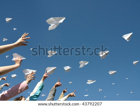 The hands of children throw upwards messages in the manner of paper airplanes. - stock photo