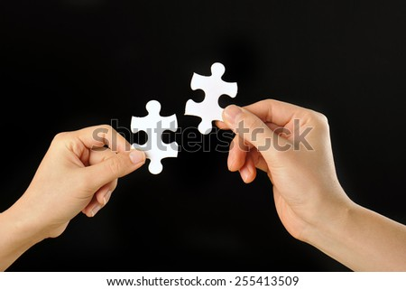 The hands of human beings that have a jigsaw puzzle that was taken with a black background