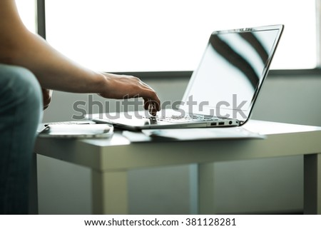 The hands of men working in stylish and classy laptop in the workplace. - stock photo