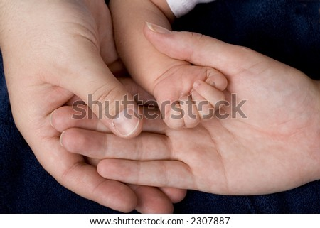 The hands of Mom, Dad, and newborn infant.