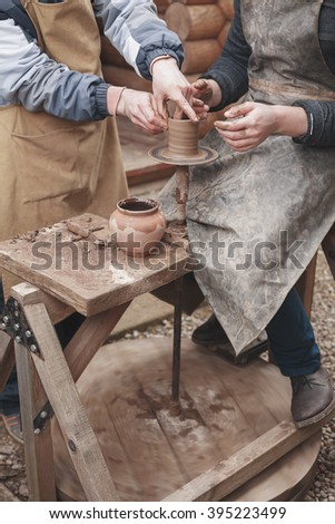 The hands of potter help make  pitcher on  pottery wheel - stock photo