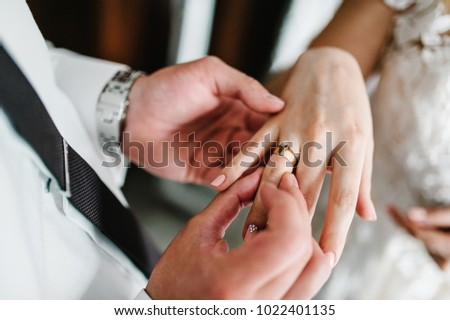 The hands of the groom wears a wedding engagement ring on the finger of the bride. Preparations. Wedding ceremony. Jewelry. close up.