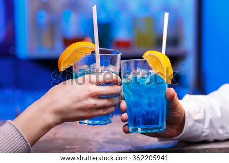 The hands with alcohol cocktails making toast on a bar background