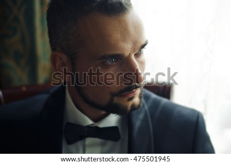 The handsome groom  sits near window in room