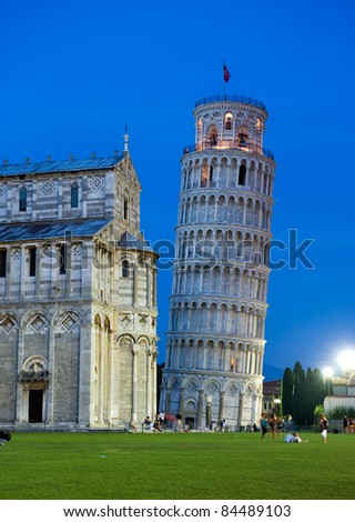 The hanging tower of Pisa with cathedral after sunset - stock photo