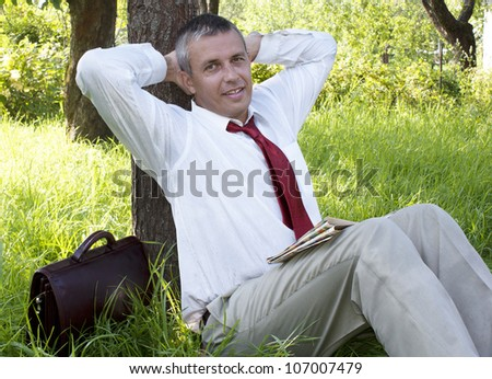 The happy adult businessman in summer green garden - stock photo