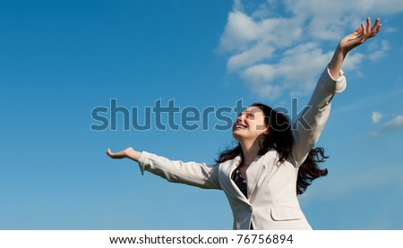 The happy attractive woman with the lifted hands. Against the blue sky