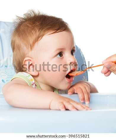 the happy baby kid boy waiting for food with spoon at table