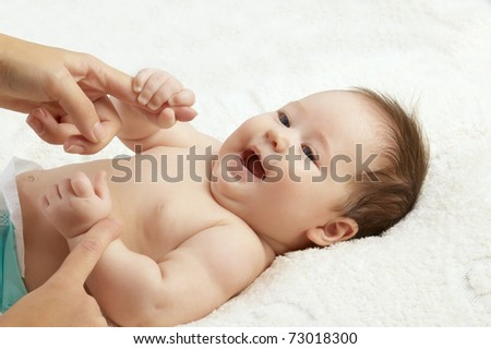 The happy baby playing with hands of mum