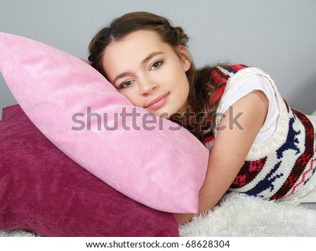 The happy beautiful girl lies on pink pillows and dreams - stock photo