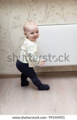 The happy boy doing first steps at home - stock photo