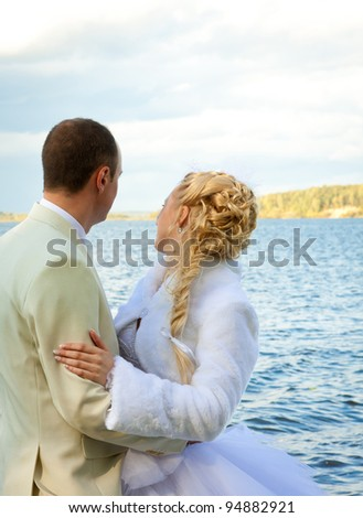 The happy bride and groom embracing and looking at water; wedding day - stock photo