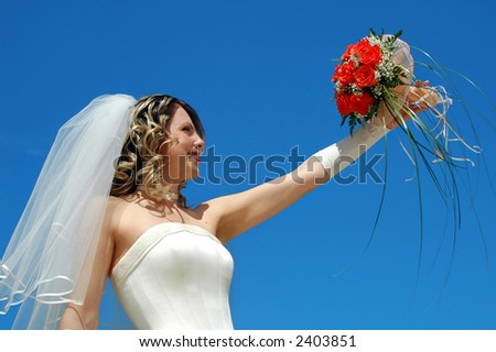 The happy bride with a bouquet of roses on a background of the sky - stock photo