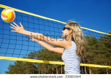 The happy cheerful girl playing with a ball at a volleyball net in motion - stock photo