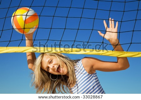 The happy cheerful girl with a ball at a volleyball net - stock photo