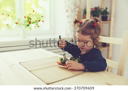 the happy child girl  eating vegetables  - stock photo