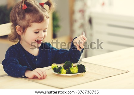 the happy child girl  eating vegetables and laughs - stock photo