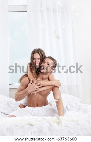 The happy couple in the bedroom with feathers - stock photo